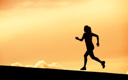 Female runner silhouette, running into sunset Stock Photos