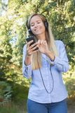 Female runner smiles while listening to music in forest Stock Photos