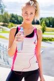 Female Runner In Sportswear Holding Water Bottle On Stairway Stock Photo