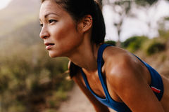 Female runner in sportswear taking a break. Close up of young asian woman resting after workout and looking away. Female runner in sportswear taking a break stock photography
