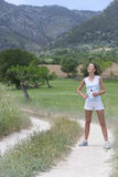 Female runner standing with water bottle on rural path royalty free stock photo