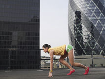 Female Runner In Start Position Against Buildings Royalty Free Stock Photo