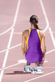 Female runner at starting block kneeling on race track Royalty Free Stock Photo