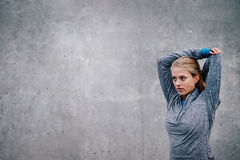 Female runner stretching arms after a running session. Young sports woman against grey background looking away stock photos