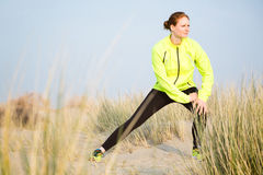 Female Runner Stretching on a Beach Stock Photos