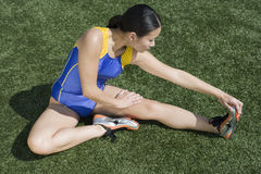 Female Runner Stretching On Field Stock Photo