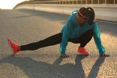 female runner stretching her legs on sunrise road Royalty Free Stock Image