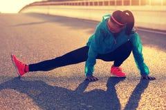 Female runner stretching her legs on sunrise road Stock Photos