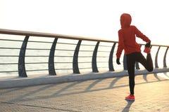 Female runner stretching her legs on sunrise seaside Stock Photography