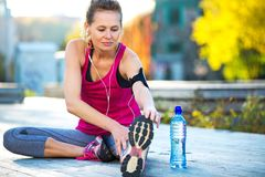 Female Runner Stretching. Before jog Royalty Free Stock Photos