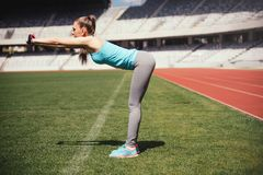 Female runner stretching, preparing for training. Fitness sportswoman warming up for running on track stock photos