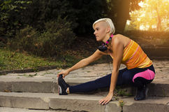 Female runner stretching at sunset in park Stock Photos