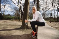 Female runner taking a break from running in forest Royalty Free Stock Photo