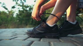 Female runner ties the laces on sheakers slow motion. Female runner ties the laces on sheakers stock footage