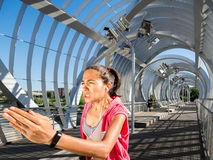 Female Runner training hard on a modern bridge. Effort, discipline and willpower concept Stock Images