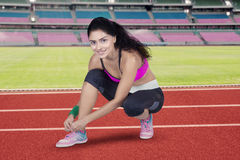 Female runner tying her shoelaces at field Royalty Free Stock Photo
