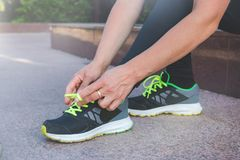 Female runner tying her shoes preparing for a run a jog outside stock photography