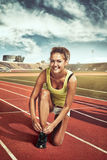 Female runner tying lace on stadium Royalty Free Stock Photography