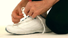 Female runner tying up her shoe laces. Close up view of a woman tying up her shoe laces in slow motion stock video