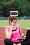 Female runner using laptop computer on the running track Royalty Free Stock Photos