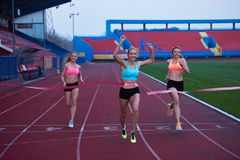 Female Runners Finishing Race Together. Female Runners Finishing athletic  Race Together Royalty Free Stock Photo