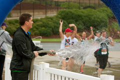 Female Runners Get Soaked By Fire Hose At Finish Line Royalty Free Stock Images