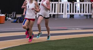 Female runners on indoor track with kinesio tape on leg. Three high school girls racing on an indoor track with one wearing kinesio tape on her leg royalty free stock images