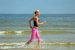 Female running on the beach Stock Photos