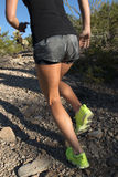 Female running up desert mountain Stock Images