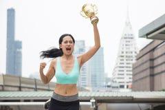 Female running winner raise gold trophy. Portrait of Asian female runner raising gold trophy to celebrate marathon running victory in Bangkok city. Happy healthy Stock Photos