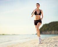Female runs along the beach Stock Photo