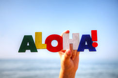 Female's hand holding colorful word 'Aloha'. Against blue background Stock Photography