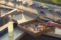 A female`s hand holds a piece of pizza on sunset and city background. Concept stock photography