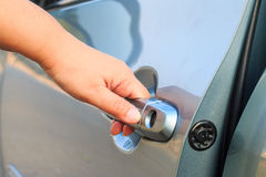 Female's hand opening a car door. Royalty Free Stock Photos