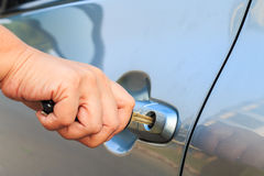 Female's hand opening a car door with car key. Stock Photos