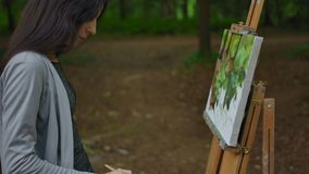 Female's hand painting a landscape on canvas in a park. Palm, brush, easel in the foreground, tree trunks of trees and greenery in the background. Stabilized stock footage