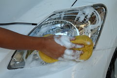 Female's hand polishing front lights of car by sponge and soap Royalty Free Stock Photo