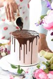 Female`s hand pouring chocolate cream on a pink cake dessert with flowers around royalty free stock images