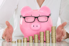 Female`s Hand Protecting Piggybank And Stacked Coins Stock Photography