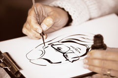 Female's hands drawing a caricature with black ink. Female's hands drawing a caricature with paintbrush and black ink on a white paper royalty free stock photography