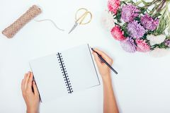 Female's hands writing in blank notepad among flat lay holiday b royalty free stock photography