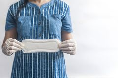 Female`s hygiene products. Woman in medical gloves holding sanitary pads against white background. Period days concept showing. Female`s hygiene products. Woman royalty free stock images