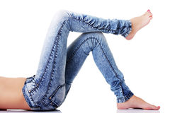 Female's legs in jeans on the floor. Side view. Stock Photo