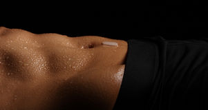 Female's sweaty abs with navel and ice cube melting. Royalty Free Stock Photography