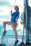 Female on sailboat. Sexy model posing on sail boat.Beautiful young woman in striped clothes Stock Photos