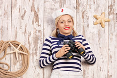 Female sailor lying on a deck and holding binoculars Stock Image
