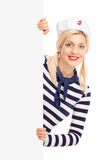 Female sailor standing behind a blank signboard Royalty Free Stock Images