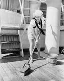 Female sailor swabbing boat deck Stock Photos