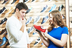 Female sale assistant demonstrates shoe to man at footwear shop. Seller female assistant demonstrate shoes to young men during footwear shopping at shoe shop stock images