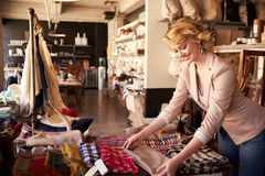 Female Sales Assistant Arranging Textiles In Homeware Store Royalty Free Stock Images